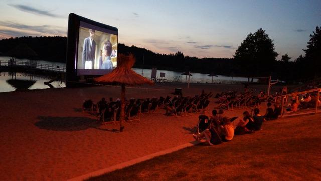 stary drewniany dom, kino letnie, wieczór, zachód słońca, ekran, plaża, woda, widownia, tłum - haart.pl blog diy zrób to sam 10
