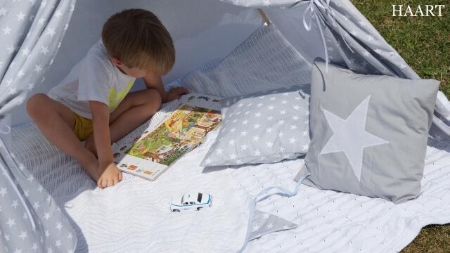 dziecko w namiocie teepee czytające książkę