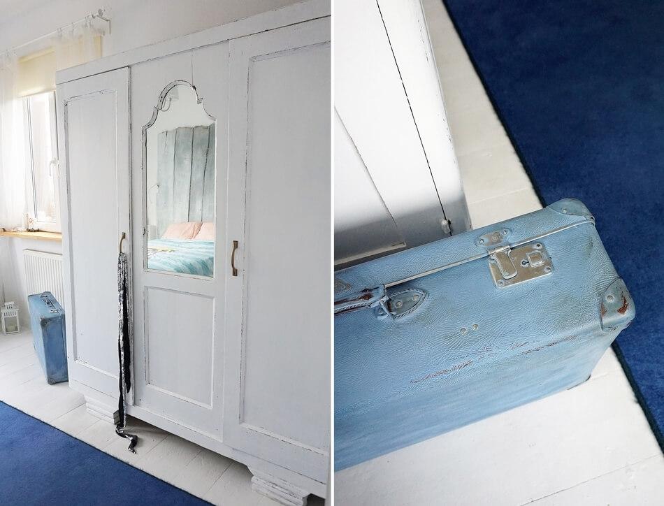 biała szafa w stylu shabby chic i niebieska walizka