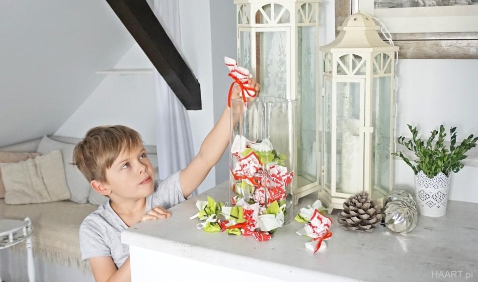 kalendarz adwentowy w wazonie. Mały chłopiec wkłada do wazonu prezent. HAART.pl blog diy