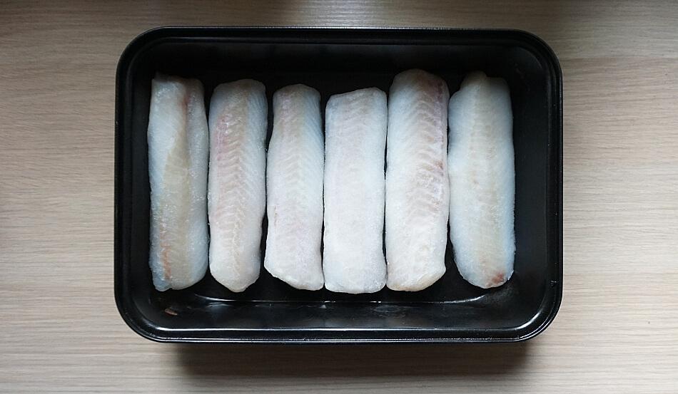 surowe filety morszczuka w brytfannie