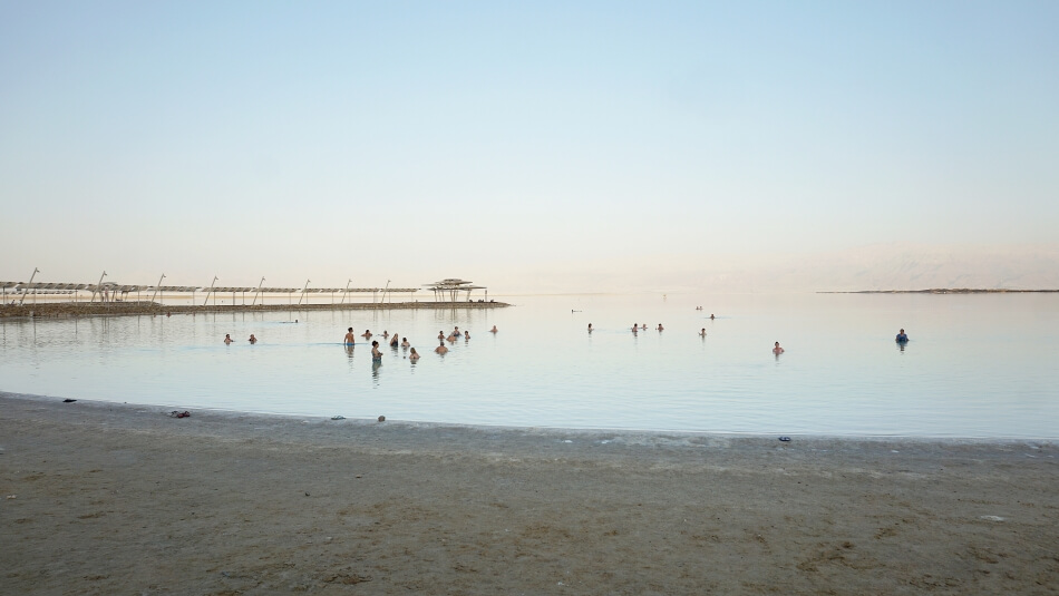 morze martwe plaża zohar beach kąpiący się ludzie zachód słońca