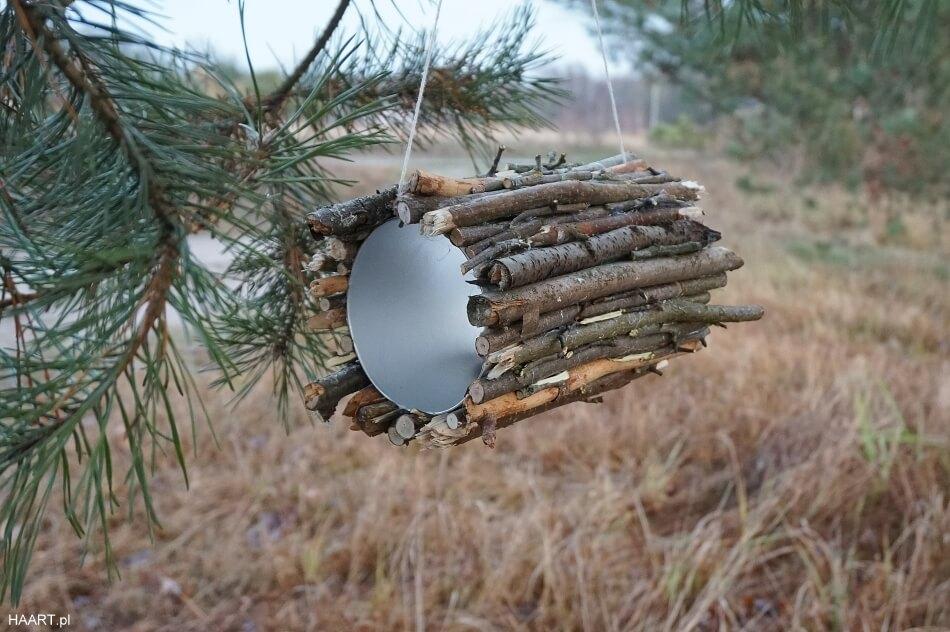 karmnik dla ptaków, tuba po musli z przyklejonymi patykami na gałęzi