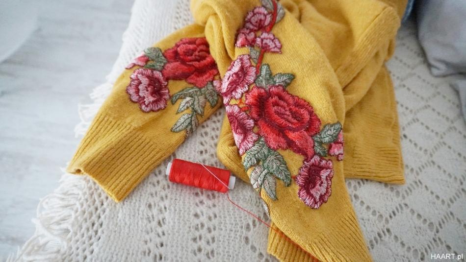 Sweter z kwiatami na rękawach