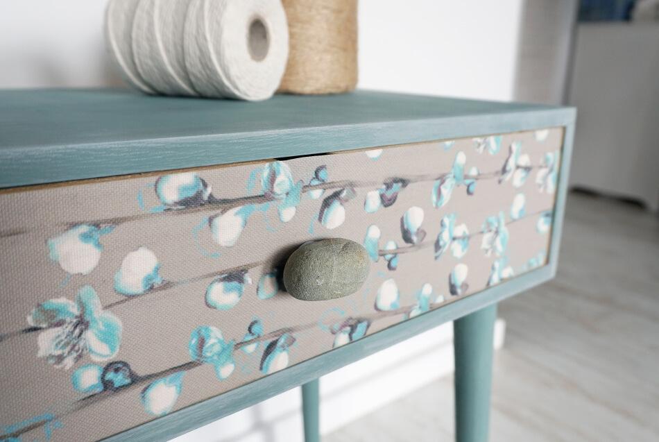 Niebieski stolik z kamieniem w roli gałki